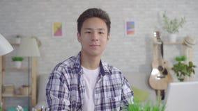 Homem asiático novo que trabalha no portátil na sala de visitas em casa e que olha a câmera video estoque