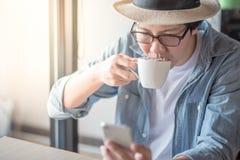 Homem asiático novo que usa o smartphone durante o tempo do café Imagem de Stock Royalty Free