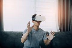 Homem asiático novo que veste vidros da realidade virtual na sala de visitas para admirar a realidade virtual imagem de stock royalty free