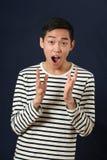 Homem asiático novo surpreendido que gesticula com duas mãos Fotografia de Stock Royalty Free