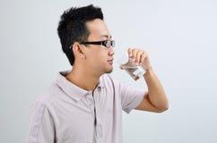 Homem asiático que bebe a água mineral Foto de Stock Royalty Free