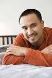 Homem asiático que encontra-se na cama. fotos de stock royalty free