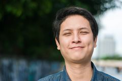 Homem asiático que está e que mostra seu sorriso feliz Fotografia de Stock