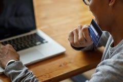 Homem asiático que guarda o cartão de crédito e que usa o laptop ao sentar-se no café Conceito em linha da compra Copie o espaço foto de stock royalty free