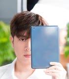 Homem asiático que guarda sua tabuleta Foto de Stock Royalty Free