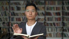 Homem asiático que guarda um blocknote que swiping no ar com uma mão filme