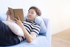Homem asiático que lê um livro para para relaxar na sala de visitas fotos de stock