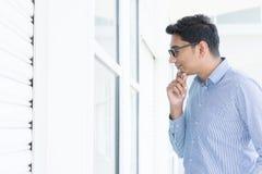 Homem asiático que olha através da janela Fotografia de Stock Royalty Free