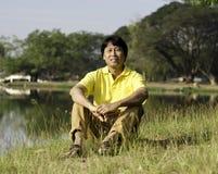 Homem asiático que senta-se no parque Foto de Stock Royalty Free