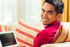 Homem asiático que senta-se no sofá que surfa o Internet Foto de Stock