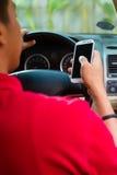 Homem asiático que texting ao conduzir Fotografia de Stock Royalty Free