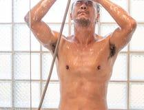Homem asiático que toma um chuveiro no banheiro imagens de stock royalty free