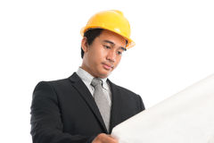 Homem asiático que veste o capacete de segurança amarelo que olha o papel da cópia azul Foto de Stock