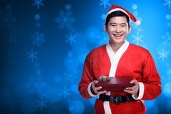 Homem asiático que veste o traje de Papai Noel que guarda a caixa de presente Fotografia de Stock Royalty Free