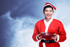 Homem asiático que veste o traje de Papai Noel que guarda a caixa de presente Imagem de Stock Royalty Free