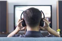 Homem asiático que veste os fones de ouvido pretos que apreciam o home entertainment imagens de stock