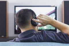 Homem asiático que veste os fones de ouvido pretos que apreciam o home entertainment imagem de stock royalty free