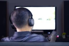 Homem asiático que veste os fones de ouvido pretos que apreciam o home entertainment foto de stock