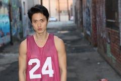 Homem asiático urbano que levanta a camiseta de alças vestindo Imagem de Stock