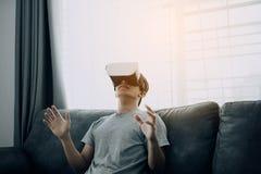 Homem asi?tico novo que veste vidros da realidade virtual na sala de visitas para admirar a realidade virtual fotos de stock royalty free