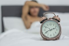 Homem asi?tico que encontra-se na cama tarde na noite, sono masculino novo no quarto em casa sono da insônia imagem de stock