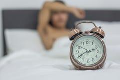 Homem asi?tico que encontra-se na cama tarde na noite, sono masculino novo no quarto em casa sono da ins?nia imagem de stock royalty free