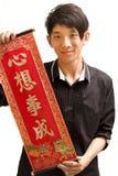 Homem asiático novo que prende a palavra afortunada chinesa para o qui Fotos de Stock