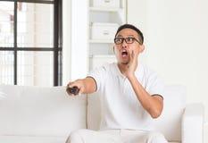 Homem asiático ocasional de Shoacked que olha a tevê Imagem de Stock