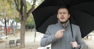 Homem asmático que usa um inalador da asma sob a chuva filme