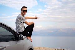 Homem assentado na capa do motor de um carro alugado em uma viagem por estrada em Israel fotografia de stock
