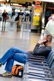 Homem assentado que fala no telefone em um aeroporto Fotografia de Stock