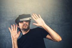 Homem assustado com os óculos de proteção da realidade virtual Fotografia de Stock