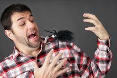 Homem assustado pela aranha falsificada Fotos de Stock Royalty Free