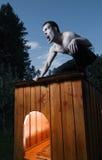 Homem assustador que senta-se no canil Imagem de Stock Royalty Free