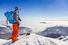 Homem ativo novo que admira a opinião do vale de um cume quando esqui Foto de Stock Royalty Free