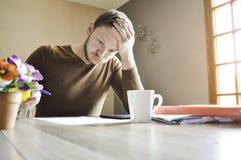 Homem ativo novo que guarda sua cabeça que trabalha duramente no documento na mesa foto de stock