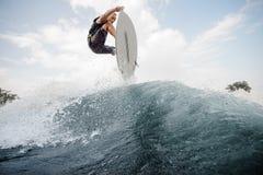 Homem ativo novo que salta acima no wakeboard branco no b alto fotos de stock royalty free