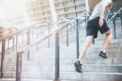 Homem ativo que escala acima as escadas em um sportswear foto de stock