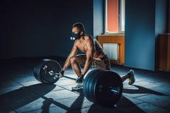 Homem atlético afro-americano que espera e que prepara-se antes de levantar o barbell pesado aptidão, esporte, treinamento, conce foto de stock
