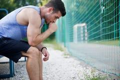 Homem atlético cansado que descansa no banco fora fotografia de stock