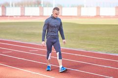Homem atlético considerável que corre no estádio da escada rolante foto de stock