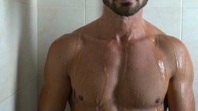 Homem atlético considerável que toma o chuveiro, relaxando em casa após o dia fatigante video estoque