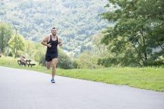 Homem atlético de sorriso que corre no parque fotografia de stock