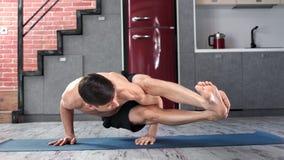 Homem atlético de sorriso que mostra o exercício da ioga na esteira na casa da cozinha que olha o tiro completo da câmera filme