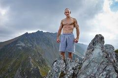 Homem atlético descamisado na parte superior da montanha fotos de stock royalty free