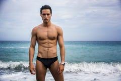 Homem atlético descamisado novo que está na água pela costa do oceano fotografia de stock royalty free