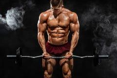 Homem atlético do halterofilista muscular forte brutal que bombeia acima os músculos com o barbell no fundo preto workout fotos de stock royalty free