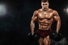Homem atlético do halterofilista muscular forte brutal que bombeia acima os músculos com peso no fundo preto workout fotos de stock