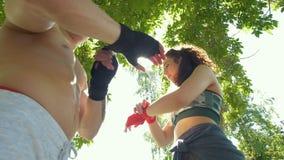 Homem atlético e mulher caucasianos que envolvem as mãos com as ataduras para o exercício no parque do verão, lento-movimento vídeos de arquivo