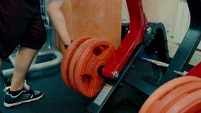 Homem atlético em um gym que trabalha em um simulador filme